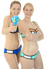 Blonde Frauen in Bikini mit Wasserpistole