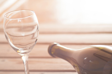 Wine glass with bottle on wooden background dreamy look