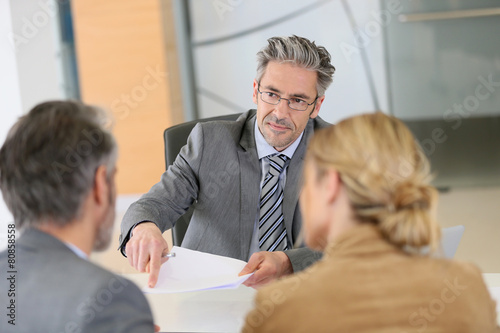 Mature couple signing contract in lawyer's office - 80858558