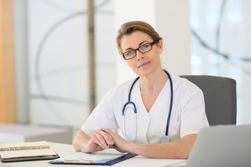 Portrait of mature nurse sitting at desk in office