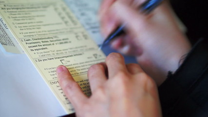 Tourist hand filling custom immigration form writing on plane