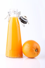 orange and a bottle of orange juice, white background
