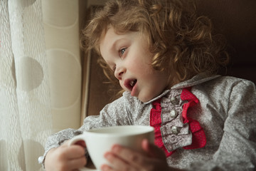Beautiful curly-haired little girl with a cup