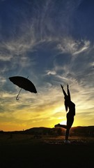 Young woman outdoors jumping with umbrella