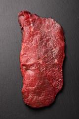 raw beef steak on black stone