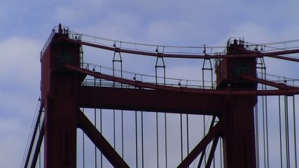 Red bridge tower top and suspender cable closeup