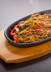 Soba noodles with meal and vegetables over black background