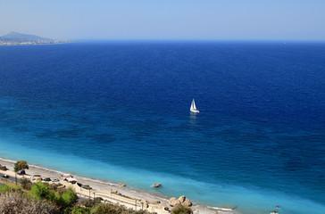 Dark blue sea and white sail . Rhodes, Greece