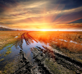 dirt road in steppe on sunset background