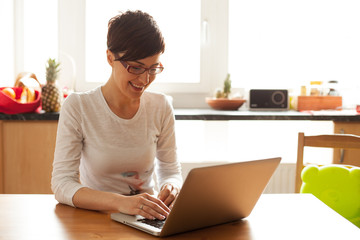 Beautiful young woman with coffee using laptop in the kitchen