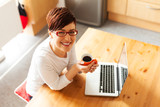 Beautiful young woman with coffee using laptop in the kitchen poster