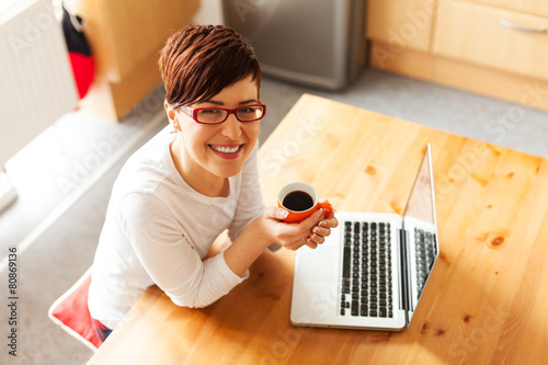 Beautiful young woman with coffee using laptop in the kitchen - 80869136