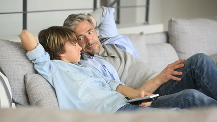 Father and son watching tv relaxed in sofa