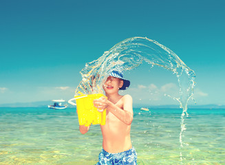 Cute cheerful child playing in sea laughing.