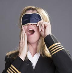 Sleepy aircrew officer yawning and using an eye shade