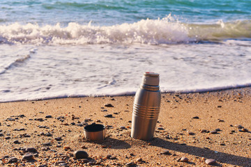 Heat protection-thermos coffee tea cup on the beach