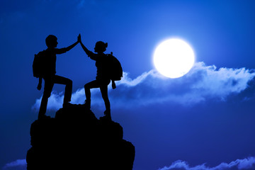 Silhouette of the two people man girl success on mountain