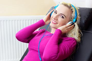 Junge blonde Frau hört Musik