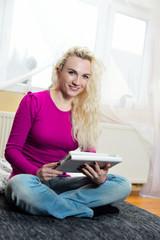 Entspannte junge Frau mit Tablet-PC auf der Couch