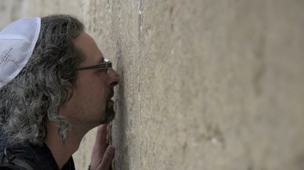 Man kissing a stones of Western wall. Slow. Jerusalem