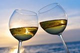 Romantic glass of wine sitting on the beach at colorful sunset - 80874552