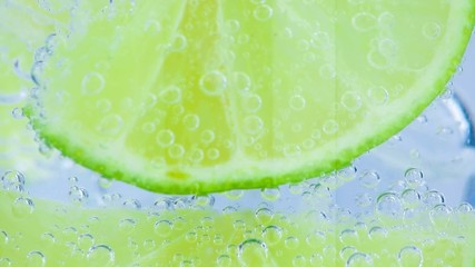 close-up of sparkling water with ice and slices lime