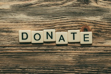 Here. Donate text on a wooden background