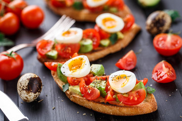 Bruschetta with tomato, avocado and quail egg