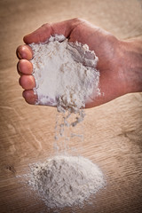 hand pouring flour on table food and drink concept