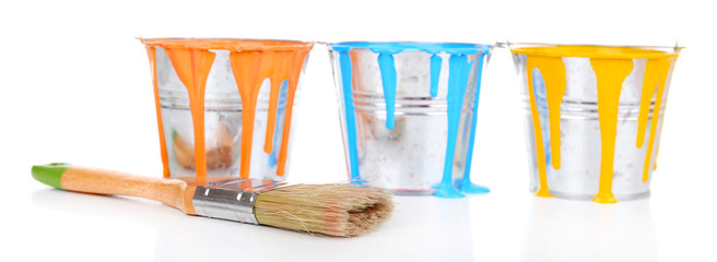 Buckets of paints with brush isolated on white