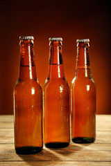 Glass bottles of beer on wooden table on dark background