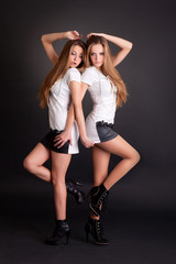 Two beautiful girls twins, isolated on black