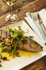 wood-fired, oven-roasted whole fish with a glass of chardonnay w