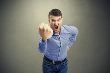 man waving his big fist and looking