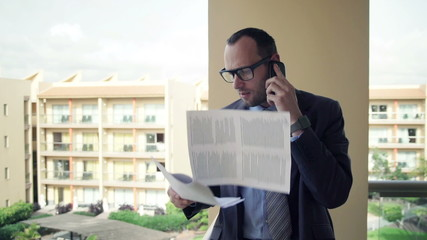 Businessman with documents talking on cellphone standing on terr