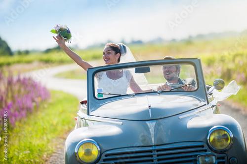 Leinwanddruck Bild A newlywed couple is driving a retro car