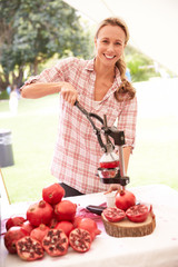 Woman Juicing Fresh Pomegranates At Farmers Market Stall