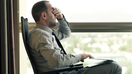 Businessman finish working on laptop, stretching and drinking co