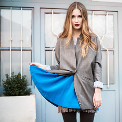 Fashion lady in jacket and blue dress posing near house