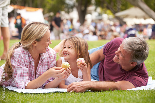 Family Enjoying Cupcakes At Outdoor Summer Event - 80883391