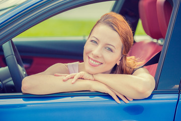 Smiling happy woman sitting in a new blue car