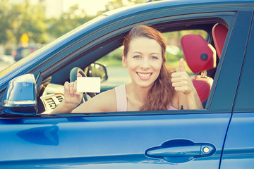 Woman driver happy showing thumbs up coming out of car window