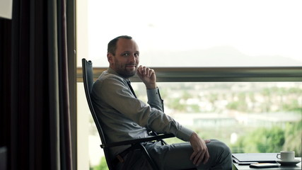 Portrait of smiling, handsome businessman sitting on terrace