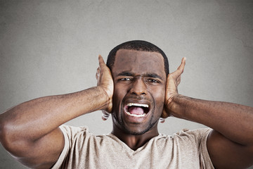 stressed young man squeezing his head going nuts screaming