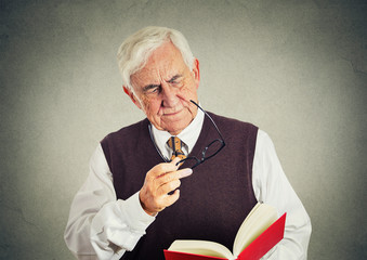 elderly man holding book, glasses having eyesight problems