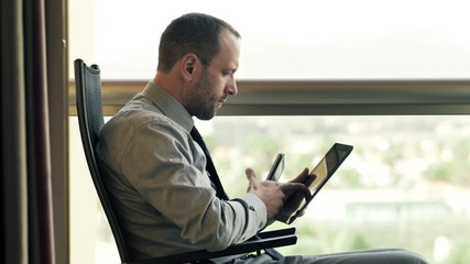 Businessman working with tablet computer and smartphone sitting
