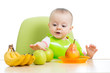 baby sitting at table with fruits