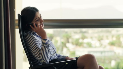 Pretty businesswoman talking on cellphone sitting on terrace