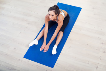 Young dark-haired athletic active sporty slim woman doing yoga