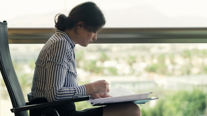 Sad, overwhelmed, businesswoman working with documents sitting o